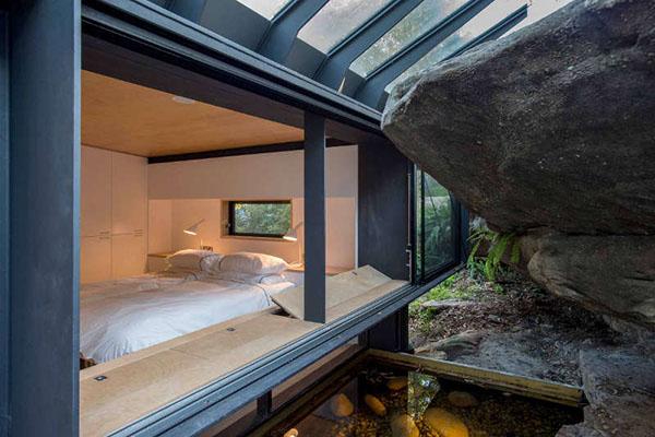 自然溢れる山に立つ黒いスチールハウス